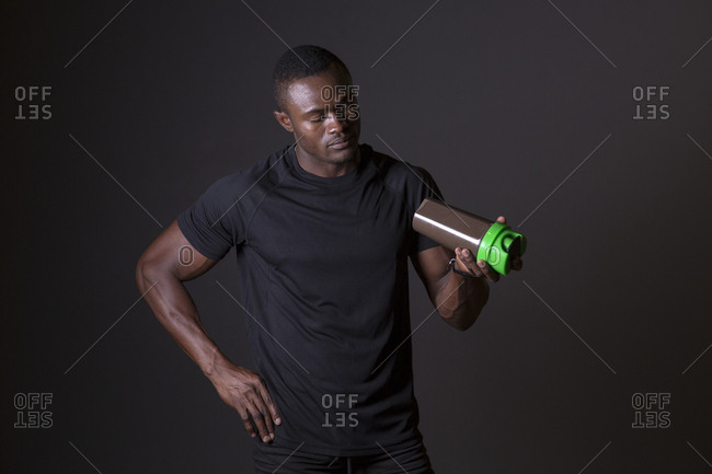 African man preparing his protein shake bottle