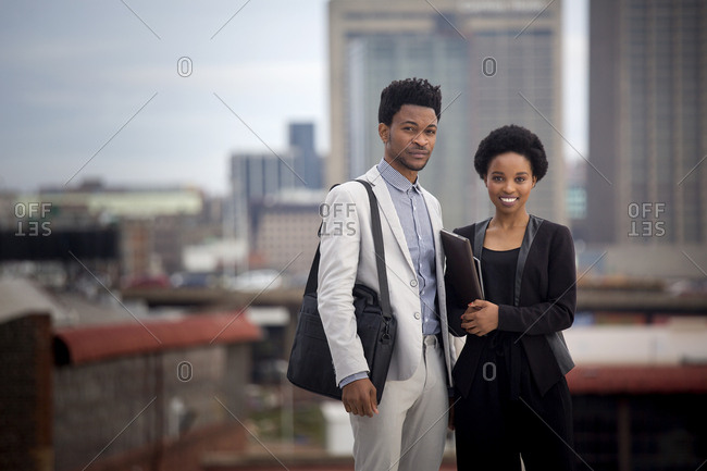 Business man and woman standing on rooftop