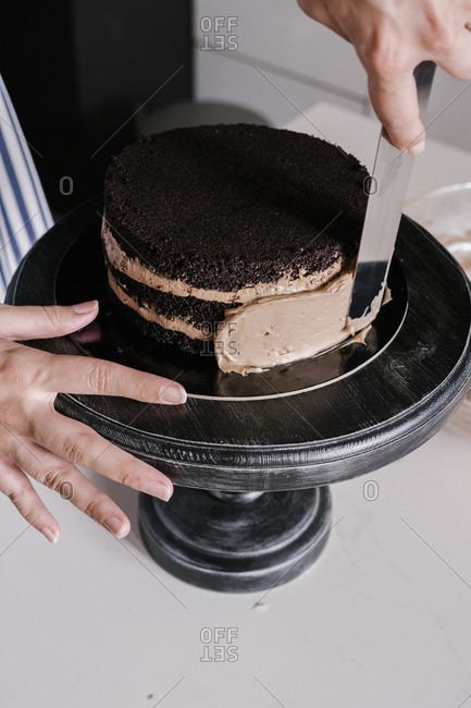 Hands frosting a chocolate cake