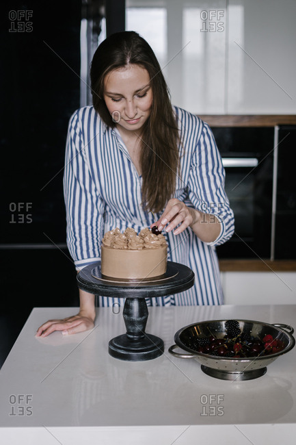 Woman topping a chocolate cake with cherries
