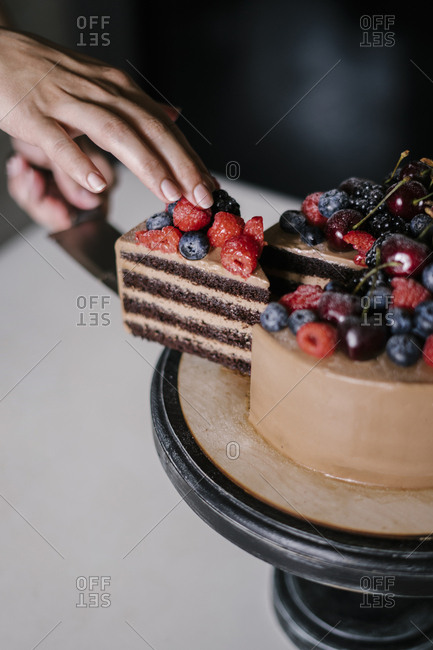Woman serving a slice of chocolate cake with berries