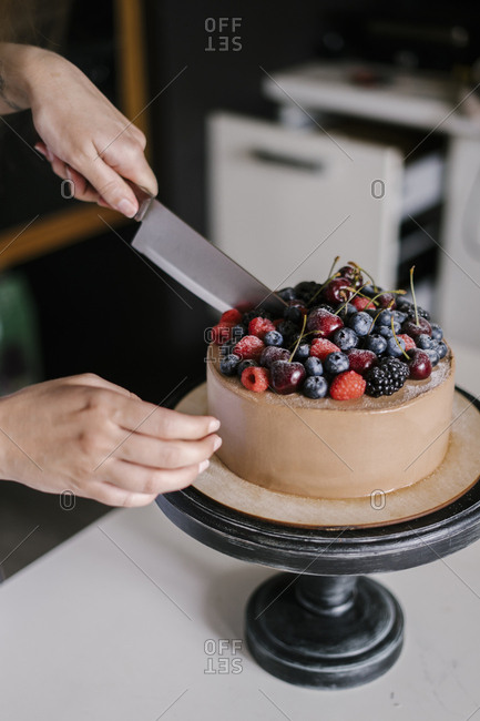 Woman slicing a chocolate cake with berries