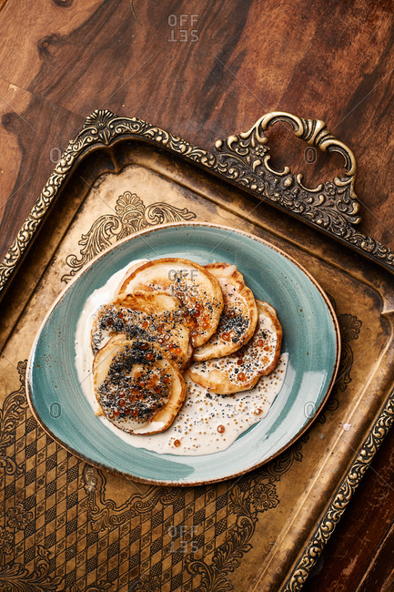 Pancakes with chia sauce served on vintage tray