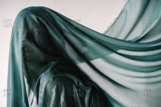 Woman covered in sheer blue cloth