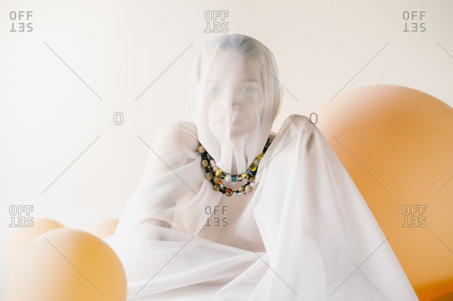 Woman covered in sheer white cloth with beaded necklaces surrounded in orange balloons
