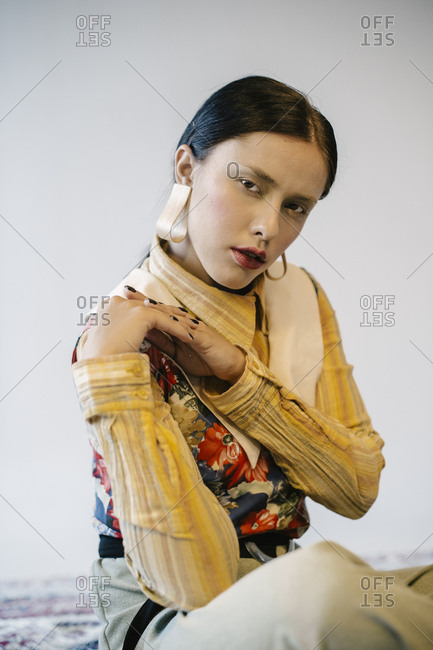 Close up of a woman wearing striped yellow blouse and floral vest