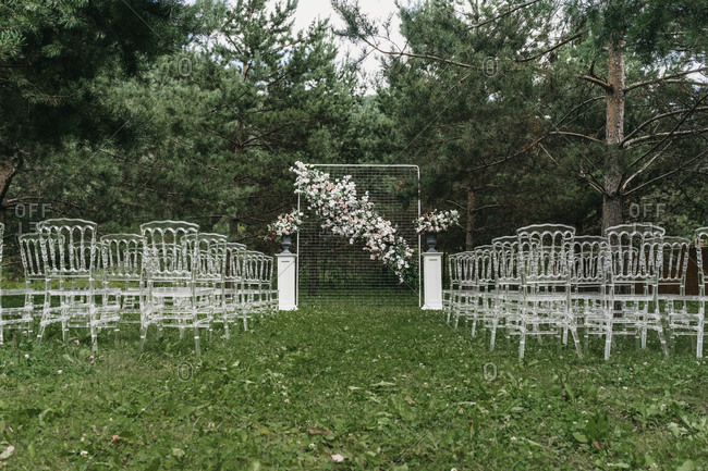 Clear chairs and a floral backdrop at an outdoor wedding ceremony