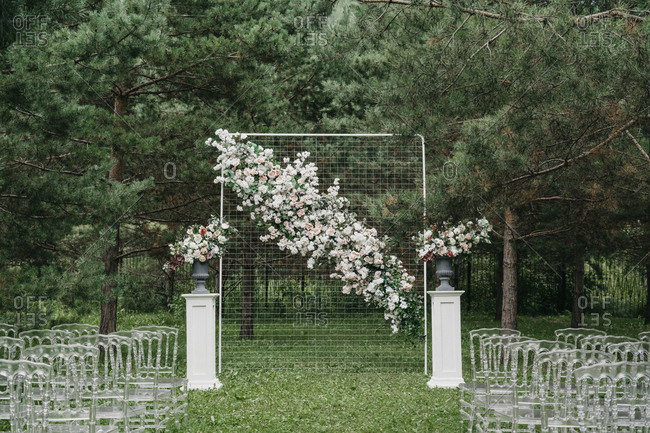 Floral alter and clear seats at an outdoor wedding ceremony