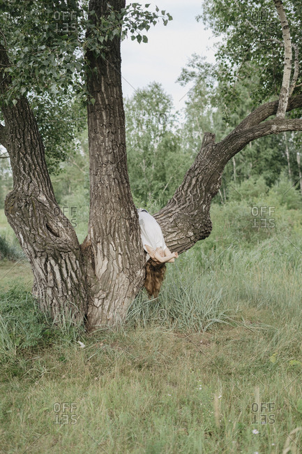 Blonde woman hanging upside down over large tree branch