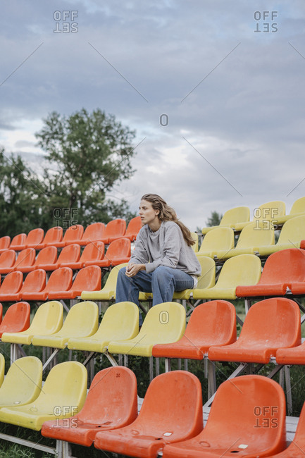 Blonde woman sitting on colorful seats at a sports field looking away