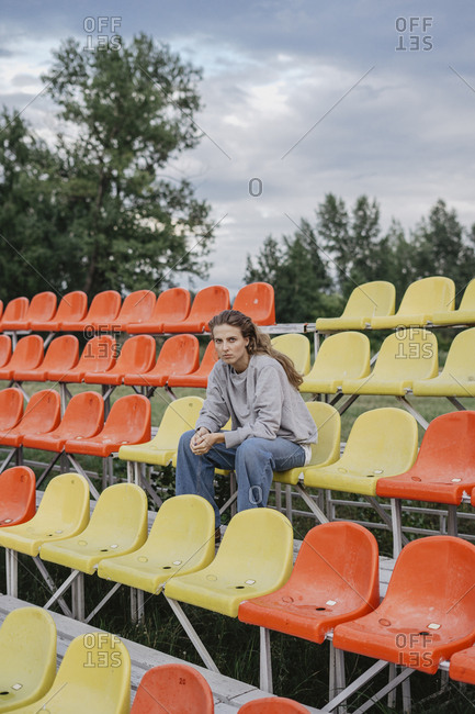 Blonde woman sitting on colorful seats at a sports field