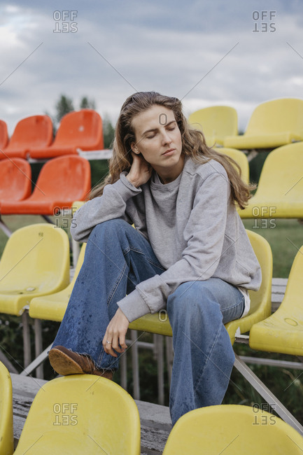 Close up of woman sitting on colorful seats at a sports field with her eyes closed