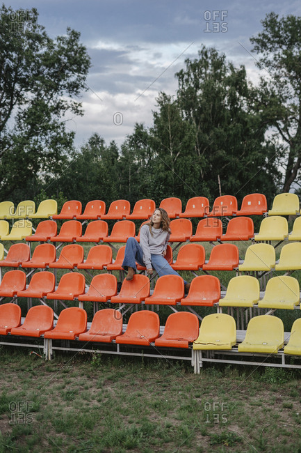 Young woman sitting on colorful seats at a sports field looking away
