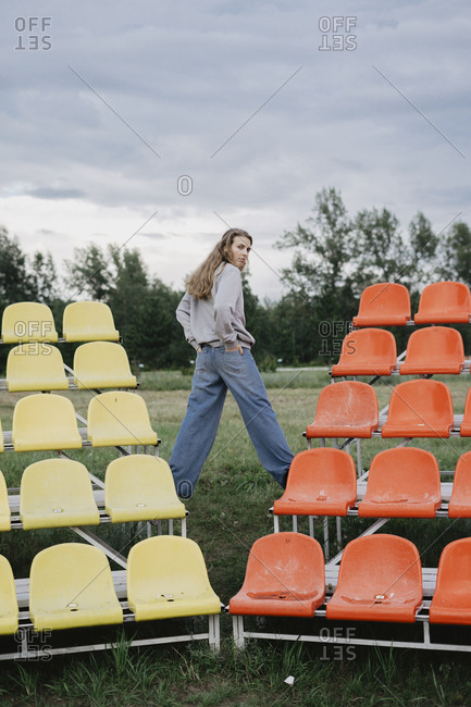 Woman standing on colorful bleachers at a sports field looking back