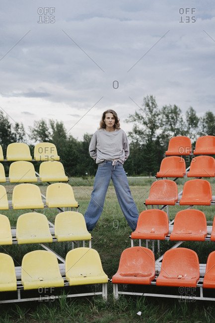 Woman standing on colorful bleachers at a sports field