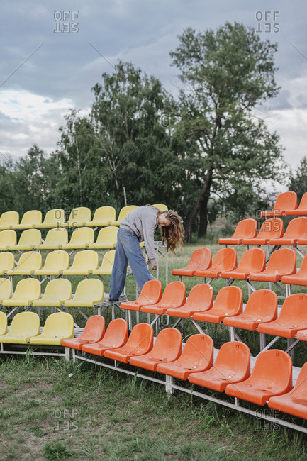 Woman standing on colorful bleachers at a sports field bending over