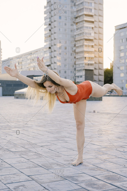 Woman doing warrior iii yoga pose on promenade