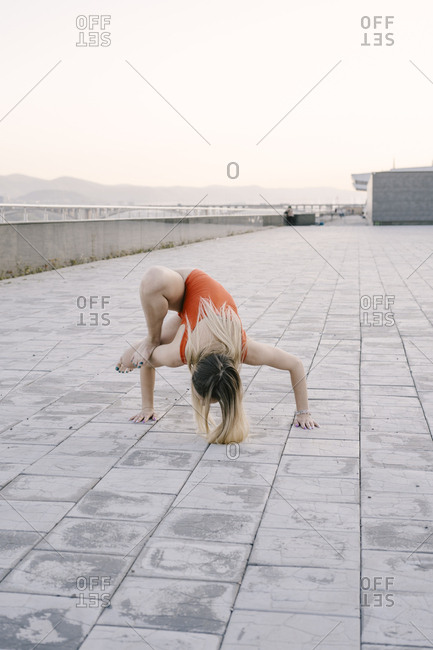 Woman doing dragonfly yoga pose on promenade