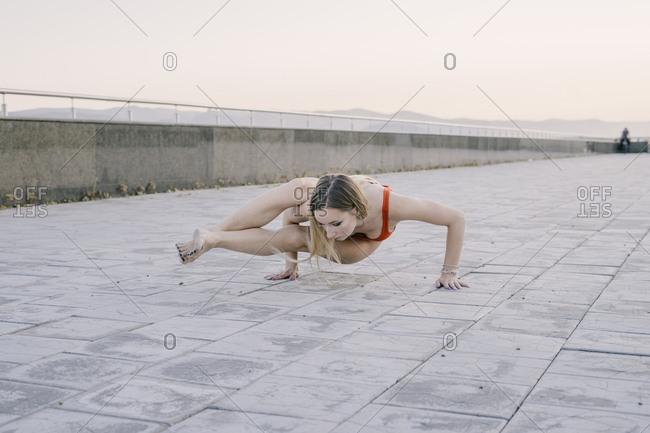 Woman doing Astavakrasana yoga arm balance on promenade