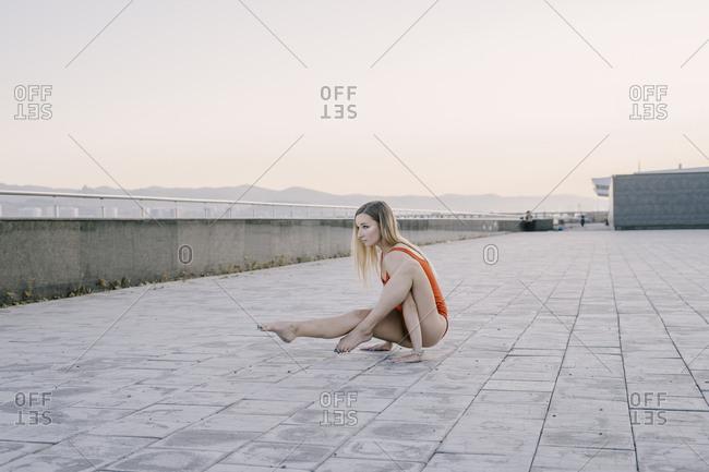 Woman doing yoga arm balance on promenade