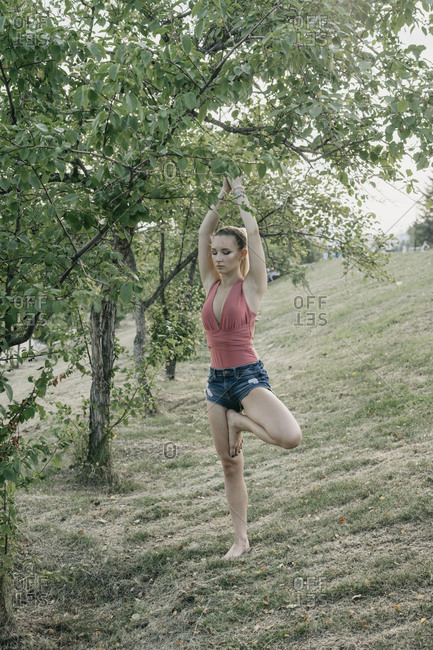 Young woman doing tree pose beside tree