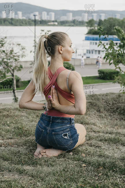Young blonde woman sitting while doing reverse prayer yoga pose