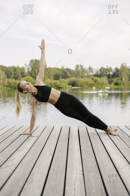 Young woman doing side plank yoga pose on riverfront while listening to music
