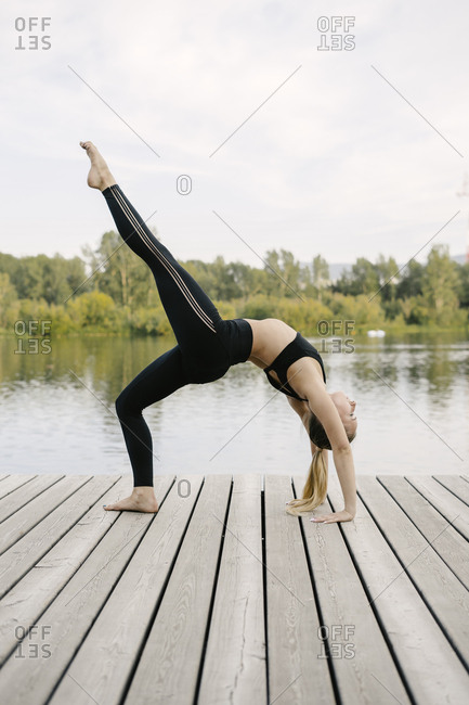 2323c1a643c2a Blonde woman doing one legged wheel pose on riverfront stock photo - OFFSET