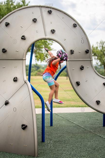 Girl jumping off climbing wall at playground