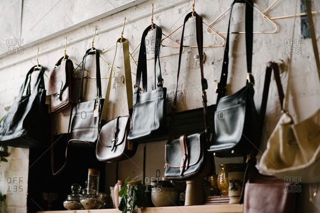Variety of purses hanging on wall in clothing shop