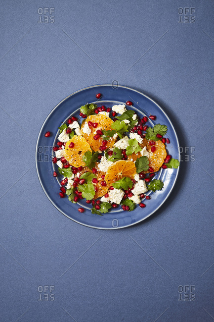 Fresh salad with oranges and feta cheese served on a blue plate