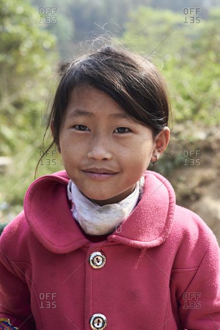 Ha Giang, Vietnam - February 15, 2018: Portrait of Hmong ethnic junior girl looking at camera wearing pink coat.