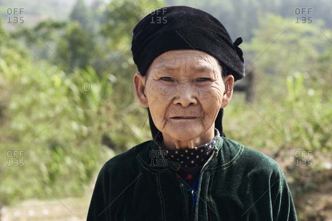 Ha Giang, Vietnam - February 15, 2018: Portrait of Hmong ethnic senior woman looking at camera wearing traditional costume.