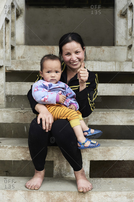 Ha Giang, Vietnam - February 18, 2018: Family portrait of a single mother and daughter sitting on a staircase barefoot and thumbs up.