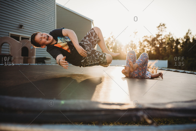 Laughing children bouncing on trampoline