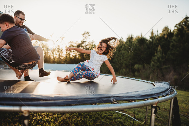 Laughing girl bouncing on trampoline with her father and brother