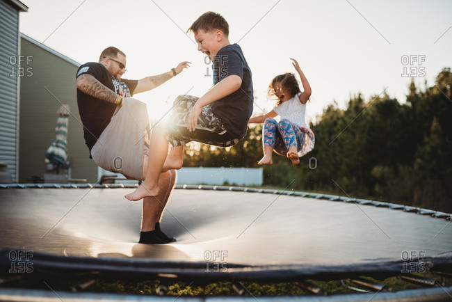 Father jumping on trampoline while bouncing children