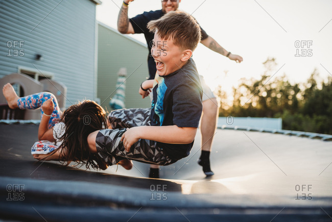 Laughing boy bouncing on trampoline with his father and sister