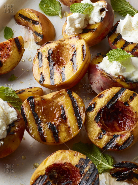 Grilled peaches and cream garnished with mint leaves