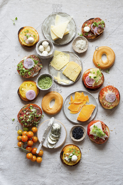 Fresh cut brightly colored heirloom tomatoes on Gluten-free bagel with cheese and onion