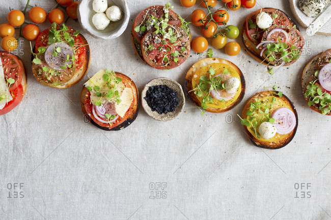 Assortment of bagels with fresh cut heirloom tomatoes with cheese and onion