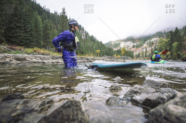 September 23, 2014: Man with paddleboard in Snake River, Jackson, Wyoming, USA