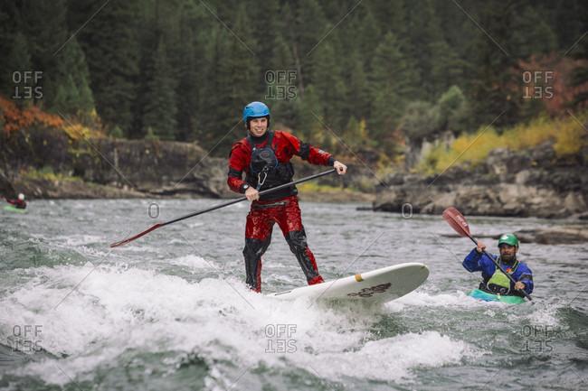 September 23, 2014: Men paddleboarding and kayaking down Snake River, Jackson, Wyoming, USA