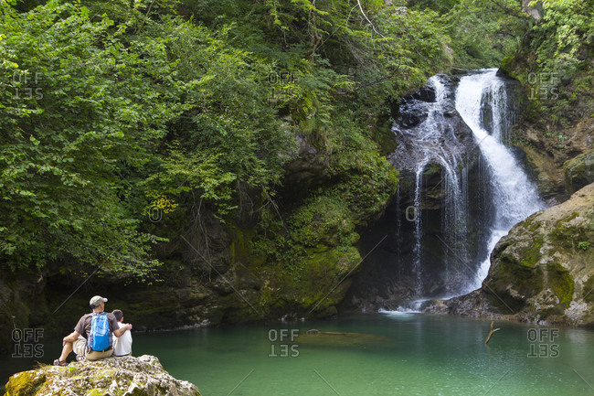 September 3, 2016: Father and son sitting on rock and looking at view of Sum waterfall in Vintgar gorge, Gorje, Bled, Upper Carniola, Slovenia