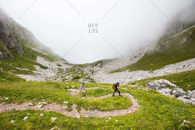 September 5, 2016: Two hikers are walking on winding trail near Mount Krn in Julian Alps, Slovenia