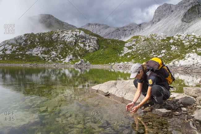 September 5, 2016: Ranger of Triglav National Park collecting drinking water from lake near Krn mountain, Slovenia
