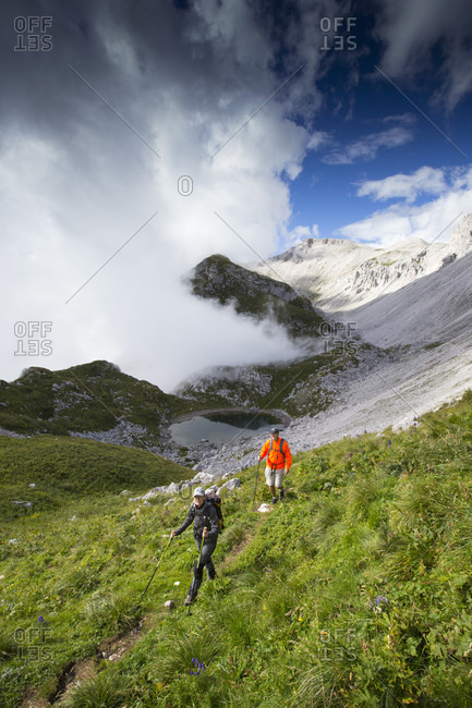 September 5, 2016: Two hikers near summit of mount Krn with dynamic weather in the background, Slovenia