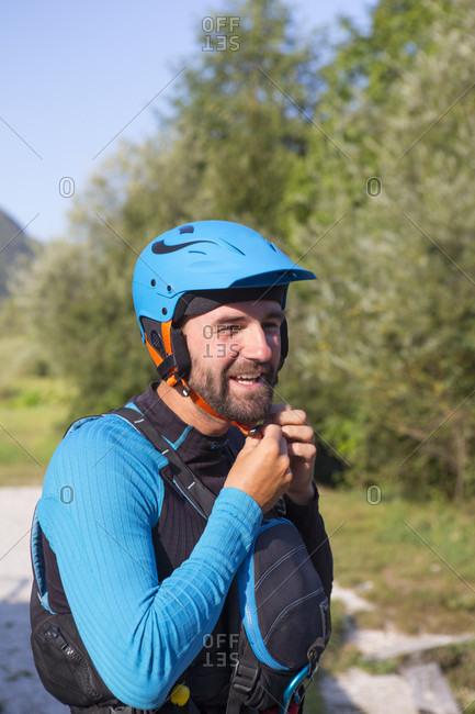September 7, 2016: Kayaker putting on helmet, Soca River near Bovec, Slovene Littoral, Slovenia