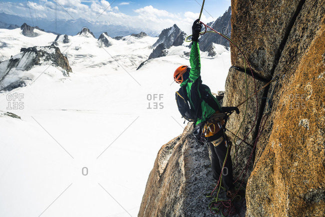 August 2, 2017: Rock climber preparing to rappel from climbing route, Aiguille Du Midi, Haute-Savoie, France