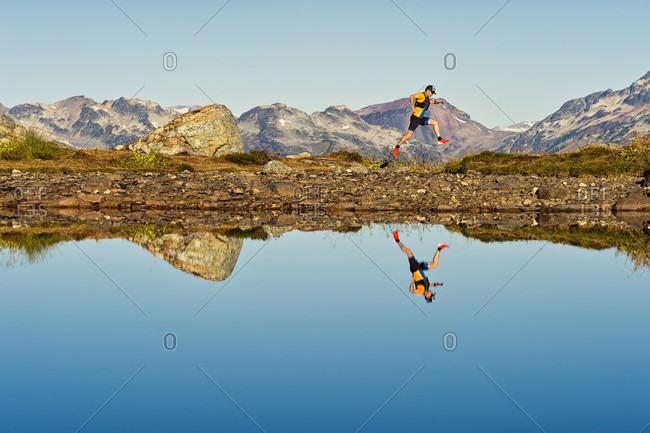 September 27, 2017: Trail runner reflecting in alpine lake, Whistler, BC, Canada